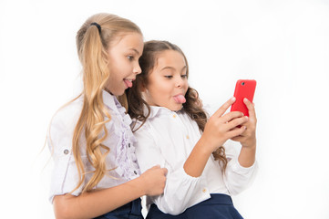 Online entertainment concept. Schoolgirls use smartphone check social networks. Send message friend. Online communication. Send selfie social network. Grimace for funny selfie. Posting funny photos