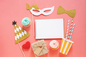 Cute party props, cake, blank notebook and gift box on colorful background, happy new year party celebration