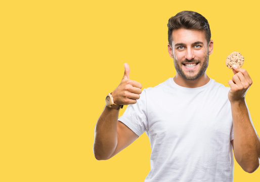 Young handsome man eating chocolate chips cookie over isolated background happy with big smile doing ok sign, thumb up with fingers, excellent sign