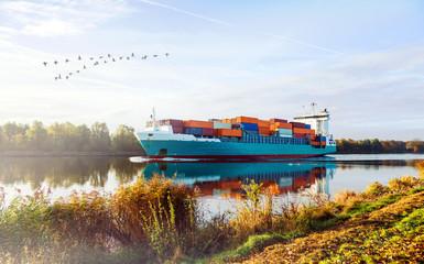 Sonnenaufgang im Herbst am Nord-Ostsee-Kanal in Schleswig-Holstein, Containerschiff auf dem Weg nach Kiel in Norddeutschland