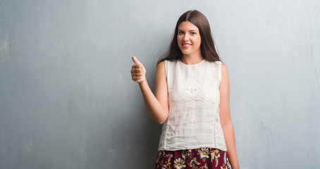 Young brunette woman over grunge grey wall happy with big smile doing ok sign, thumb up with fingers, excellent sign
