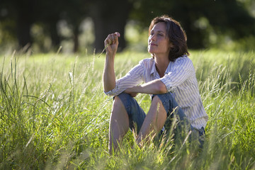 Thoughtful mature woman sitting in field of grass in countryside