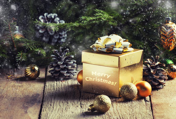 Christmas or New Year gold gift box, with festive decorations and Christmas balls on the background of green spruce, selective focus