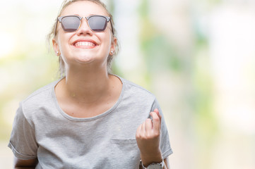 Young blonde woman wearing sunglasses over isolated background very happy and excited doing winner gesture with arms raised, smiling and screaming for success. Celebration concept.