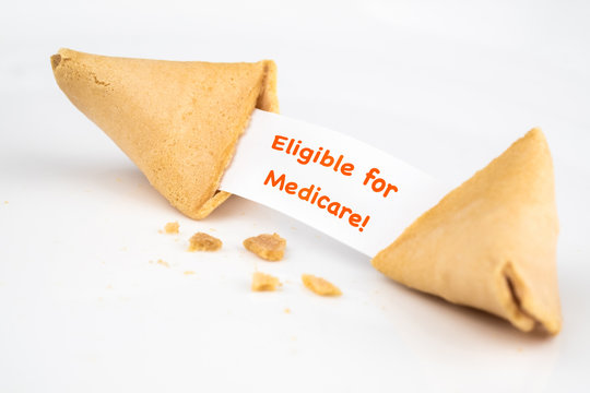 """CRACKED FORTUNE COOKIE WITH WORD """"Eligible for Medicare!"""" ON WHITE SLIP PAPER / HEALTH CARE CONCEPT"""