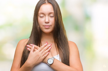 Young caucasian beautiful woman over isolated background smiling with hands on chest with closed eyes and grateful gesture on face. Health concept.