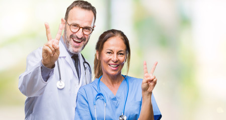 Middle age hispanic doctors partners couple wearing medical uniform over isolated background smiling with happy face winking at the camera doing victory sign. Number two.