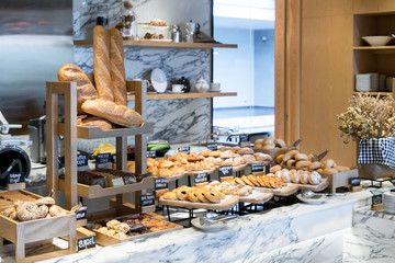 A variety of fresh homemade bread and bakery corner in luxury hotel breakfast buffet, restaurant interior.