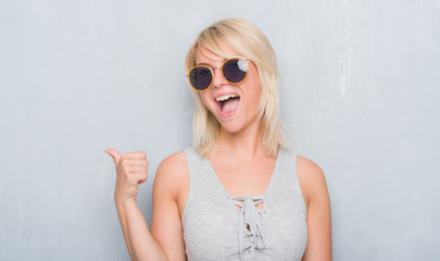 Adult caucasian woman over grunge grey wall wearing retro sunglasses pointing and showing with thumb up to the side with happy face smiling
