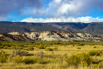 Gorgeous cliffs, fields of autumn grasses, and mountains in evening light at Browns Park National Wildlife Refuge in northwestern Colorado