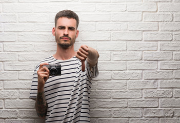 Young man holding vintage camera standing over white brick wall with angry face, negative sign showing dislike with thumbs down, rejection concept