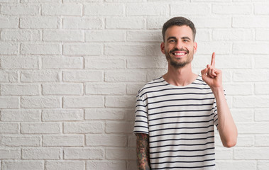 Young adult man standing over white brick wall surprised with an idea or question pointing finger with happy face, number one