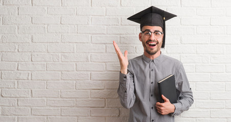 Young adult man over brick wall wearing graduation cap very happy and excited, winner expression celebrating victory screaming with big smile and raised hands