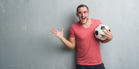 Young caucasian man over grey grunge wall holding soccer football ball very happy and excited, winner expression celebrating victory screaming with big smile and raised hands