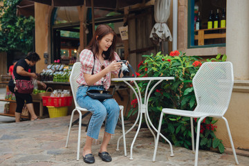Happy woman traveler checking camera sitting in outdoors cafe in retro vintage city in thailand.