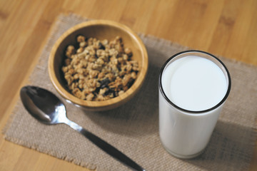 fresh milk in the glass with muesli background