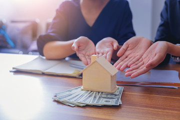 Business Real Estate Concept, House model with dollar bills with hands offering to you