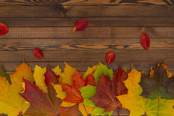 Autumn background of fallen leaves and berries on an old wooden table. The concept of thanksgiving