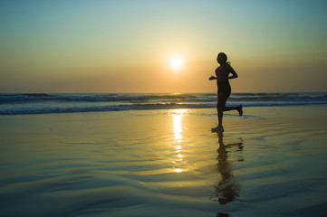 silhouette of young happy and attractive African American runner woman exercising in running fitness workout at beautiful beach jogging and enjoying sunset