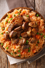 Authentic Mexican rice with green peas and carrots served with spicy pork close-up on a plate. Vertical top view