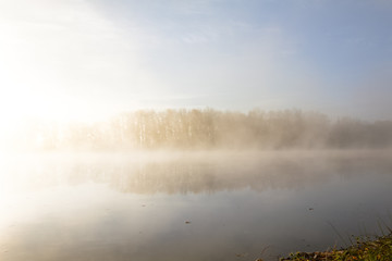 Morning autumn scenery on the bank of the river, wrapped in fog, through which the rays of the sun make their way.