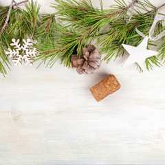 Christmas background with fir tree branches, cones, snow, xmas decorations, a champagne cork, and copy space