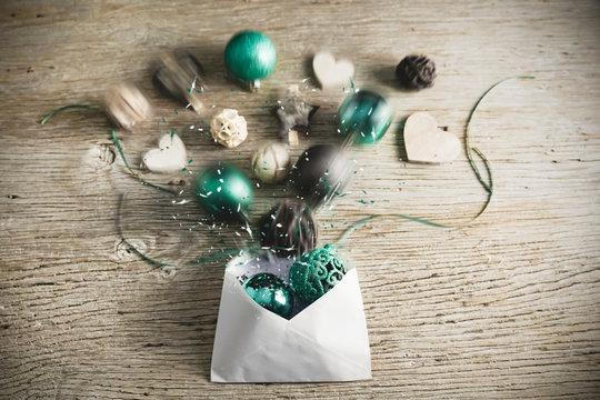 Ein Brief zu Weihnachten wird geöffnet. Die türkis farbigen Weihnachtskugeln und Holzelemente spritzen heraus. Fröhliche Nachricht zu Weihnachten.