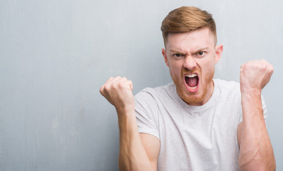 Young redhead man over grey grunge wall annoyed and frustrated shouting with anger, crazy and yelling with raised hand, anger concept