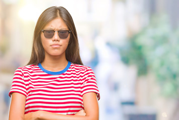 Young asian woman wearing sunglasses over isolated background skeptic and nervous, disapproving expression on face with crossed arms. Negative person.