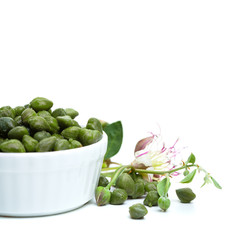 Organic capers in white bowl on white background