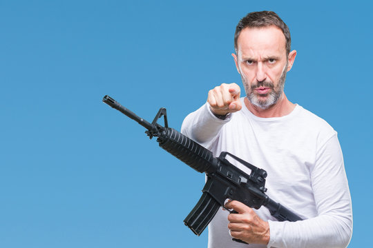 Middle age senior hoary criminal man holding gun weapon over isolated background pointing with finger to the camera and to you, hand sign, positive and confident gesture from the front