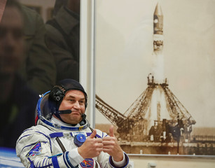 International Space Station (ISS) crew member and cosmonaut Alexey Ovchinin of Russia gestures after donning a space suit shortly before a launch at the Baikonur Cosmodrome