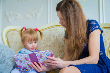 Young mother and her baby daughter looking photobook togerher at home. Family, childhood and leisure concept