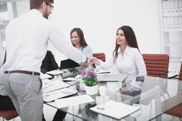 man and woman partners shaking hands over the table, maintaining eye contact