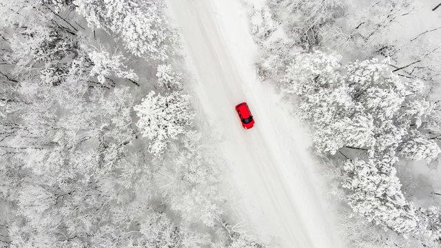 rotes Auto auf einer schneebedeckten eisigen Straße im Winter von oben, Luftbildaufnahme
