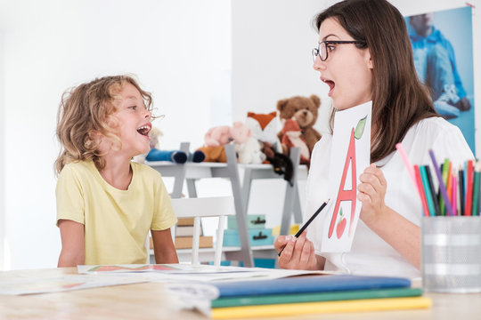 A happy child pronouncing a letter during speech therapy with a specialist.