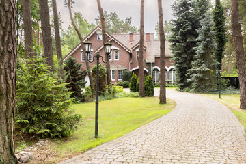A long cobbled driveway in woods leading to an English style house.