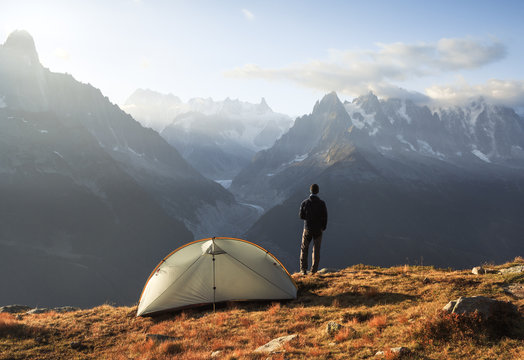Hiker enjoying the view and a cup of coffee at his campsite on the famous Tour du Mont Blanc.
