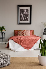 Poster on grey wall above bed with red sheets in bedroom interior with pouf and plants. Real photo
