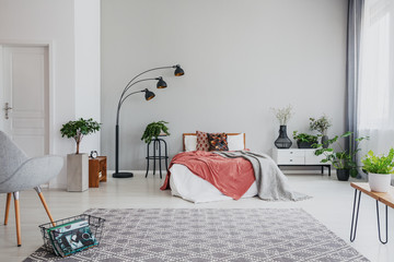 Armchair and carpet in apartment interior with plants and lamp next to bed with red sheets. Real photo