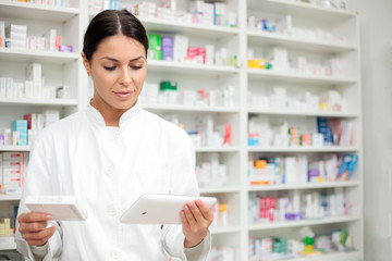 Medicine, pharmaceutics, health care and people concept - Young pharmacist holding a tablet and box of medications.