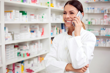 Beautiful young female pharmacist talking on the phone, shelves with medications in the background