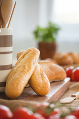 Close-up on baguette on wooden desk during breakfast with blurred tomatoes. Real photo