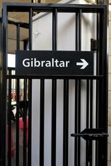 Gibraltar, panneau avec flèche sur porte noire en fer