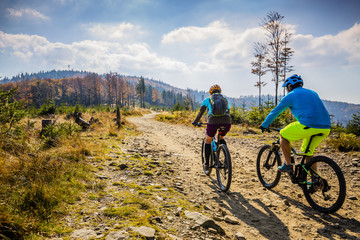 Foto auf AluDibond Radsport Mountain biking woman and man riding on bikes at sunset mountains forest landscape. Couple cycling MTB enduro flow trail track. Outdoor sport activity.