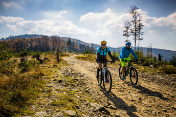 Wall Mural - Mountain biking woman and man riding on bikes at sunset mountains forest landscape. Couple cycling MTB enduro flow trail track. Outdoor sport activity.