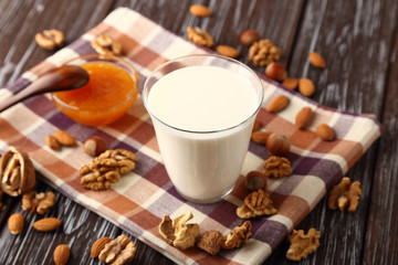 A glass of fresh milk with almonds, hazelnuts, walnuts and honey.