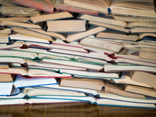 a stack of opened book, lying on the table. Knowlege and education concept