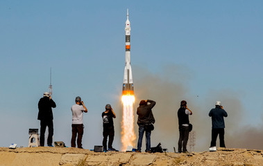 Photographers take pictures as the Soyuz MS-10 spacecraft carrying the crew of astronaut Nick Hague of the U.S. and cosmonaut Alexey Ovchinin of Russia blasts off to the International Space Station (ISS) from the launchpad at the Baikonur Cosmodrome