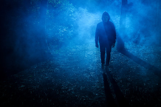 Halloween concept. Man Maniac in white mask and black hood in the forest under the blue light of the moon and fog at night, look.